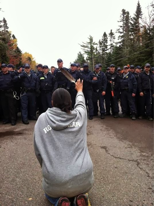 Native American women warriors are risking everything to protect the water, the land, and the future generations – for all of us. This image of Amanda Polchies at a Mi'kmaq protest against potential fracking near Elsipogtog First Nation in New Brunswick, Canada, taken by reporter Ossie Michelin, went viral.